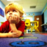 Photo description: Young toddler laying down on a carpet in a daycare.