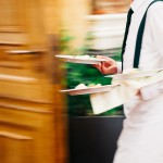 Photo of waiter carrying plates to a table with a speed blur. Photo credit: Mark Umbrella