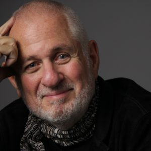 Portrait of Richard Saul Wurman looking at the camera and his hand resting against his head.
